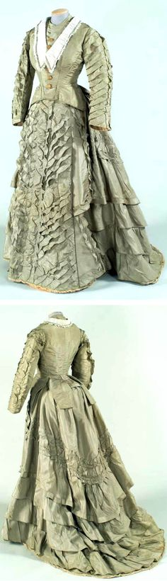 Day dress ca. 1887. Light olive green silk satin bodice and skirt with a long train and bustle, trimmed with rows of ruffles on sleeves and down the front of skirt. Gregg Museum, North Carolina State Univ.