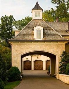 Porte-cochere, stone, garage beyond, arched, cupola, mansard dormer, elegant cottage style