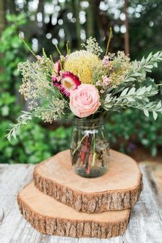 Boho chic rustic affordable wedding centerpieces by simply using roses, green filler flowers, olive branches, and a mason jar.
