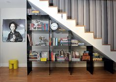 O espaço sob a escada geralmente sofre com a pouca altura. E como a área pode ser significativa, seria um desperdício não aproveitá-la. Os arquitetos Marcos Marcelino e Roberta Martins sugerem uma estante metálica