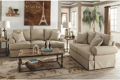 """The Kinning - Flax Sofa from Ashley Furniture HomeStore (AFHS.com). With the casual contemporary slipcover look along with the light twill fabric, The """"Kinning-Flax"""" upholstery collection features large rolled set-back arms and supportive boxed cushions that add comfort to the relaxed airy design this furniture brings to any home's décor."""