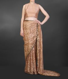 Nude chantilly lace saree with sequin detailing and green backing teamed up with a nude sleeveless blouse.