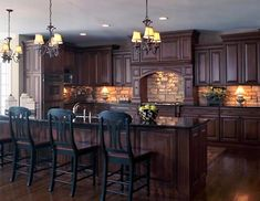 Achieve a country manor look with stone walls, lamp-style chandeliers and wood cabinets with a dark brown stain