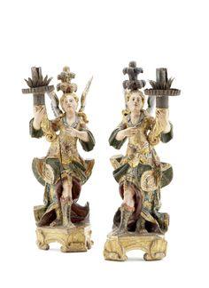 Invulgar par de anjos candelários, esculturas portuguesas do séc. XVIII, em madeira entalhada, policroma e dourada, sobre base entalhada e dourada. Arandelas e copos das velas em folha.  Alt. aprox.: 40 cm.