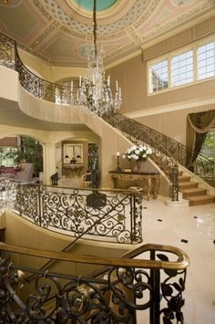 Stunning Wayzata Bay, Minn., grand foyer by John Kraemer & Sons featuring a domed, decorative ceiling and individual wrought-iron staircases for the upper and lower levels of the house. #interior #staircase #ceiling #luxury
