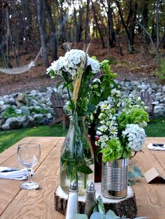 North Country Vintage wood slices and tin cans with antique bottles make sweet centerpieces.