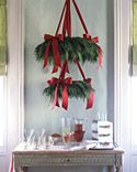"""This Scandinavian-style greenery """"chandelier"""" is an eye-catching way to draw guests to a holiday cocktail or buffet table. It's fashioned from a pair of cedar wreaths that have been adorned with wine-colored satin bows and suspended from the ceiling with lengths of the same ribbon."""