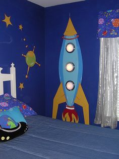 outer space theme room with painted rocket ship and lights attached