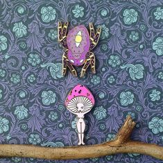 Suprise!  . . . [Image description: a spider cat enamel pin and a mushroom girl enamel pin by @gildedcreaturesart  on patterned paper with a twig] . . . #enamelpins #lapelpins #pingame #pinstagram #enamelpin #lapelpin #hardenamelpin #pinart #collector  #pin #pins #pinbadge #pincollector #pincollection #pincollage #pinaddict #pinsofig  #hatpin #hatpins  #pinlife #pincommunity #mushrooms #mushroom #fungi #mushroomart #mushroompins