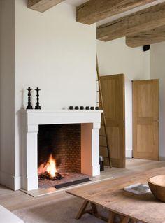 large open fireplace, let ook op de zware balken De schouw komt een eind de kamer in, maar dat is niet hinderlijk.