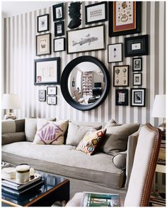I love the striped wall and grouping of frames and photos.