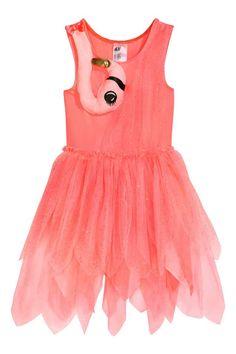 Dansjurk: Een mouwloze dansjurk van tricot en glittertule met een licht gewatteerde applicatie in de vorm van een flamingo bovenaan. De jurk heeft een naad in de taille met een tulen biesje met een overlocksteek en een rok van meerdere lagen tule met een asymmetrische snit. De rok is gevoerd.
