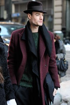 Shop this look on Lookastic:  https://lookastic.com/men/looks/overcoat-crew-neck-sweater-dress-pants-hat-scarf/6056  — Black Wool Hat  — Black Scarf  — Dark Green Crew-neck Sweater  — Burgundy Overcoat  — Black Dress Pants