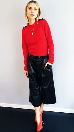 Pernille Teisbaek wears a red sweater with black button detailing on the shoulder, high-waisted leather culottes, and red suede pumps
