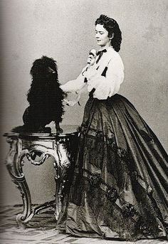 Empress Elizabeth, in 1864, playing with a dog.