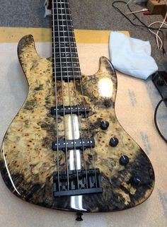 Sadowsky Guitars Ltd.  Master grade Buckeye Burl top and Ebony board with black pearl block inlays.