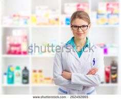 Portrait of confident woman pharmacist wearing uniform selling medicines and cosmetics in her retail shop.