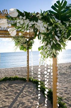 Great beachy wedding arbor with tons of lilies, monstera foliage, stock, and then some capiz shell streamers. Very nice!