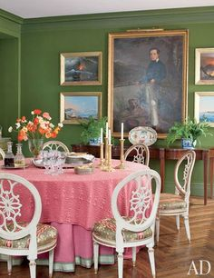 An ancestral portrait and 19th-century reverse-painted-glass studies of Naples and Vesuvius are set off by the moss-green wool-covered walls in the dining room of Fernanda Kellogg and Kirk Henckels's Manhattan apartment | archdigest.com
