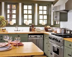 Light-colored wood counters paired with green cabinets and windows make this kitchen inviting.