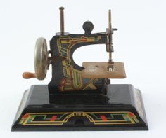 "Lot 34 in the 6.17.14 online & live auction! Vintage miniature toy Casige Children's portable flatbed hand crank sewing machine No. 116. Made in Germany it features a painted black metal body with red, green and gold toned Art Deco style decals. It is in excellent condition and appears to be intact including the needle. Original paint with light oxidation / rust on the sewing platform. Machine measures 7.75"" tall x 8.5"" wide x 5"" deep. #Decor #Home #POGAuctions"