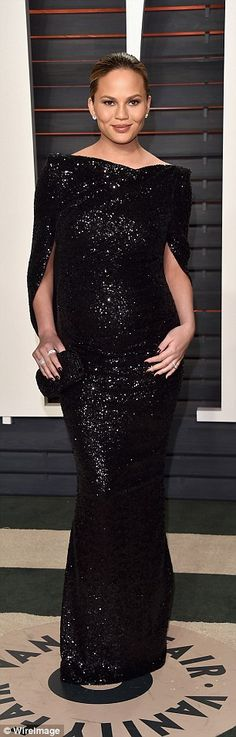 Blooming lovely: Chrissy swapped her exquisitely detailed red Marchesa gown for a classy black sequinned number which covered up her burgeoning bump