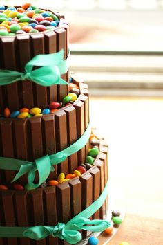 M/Kit Kat Cake (Instructions: Place Twix bars around 3 increasingly larger empty tubs & secure w/ribbon. Fill each tier w/M 'til full. Place each tier on top of the other to create cake.) YOU HAD ME AT KIT KAT. Pretty Cakes, Cute Cakes, Beautiful Cakes, Amazing Cakes, It's Amazing, M&ms Cake, Cupcake Cakes, Cake Kit, Bolo Grande