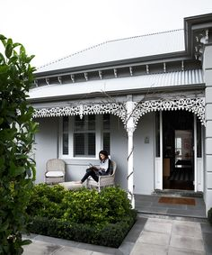 Georgina's monochrome home renovation:Georgina Austin relaxes with a book on the front verandah of her double-fronted brick Victorian home in Prahran, Melbourne.