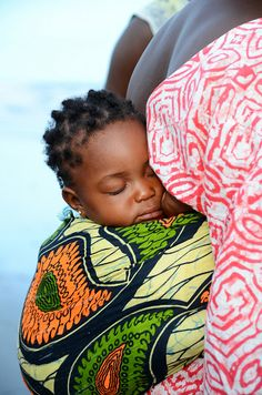Baby girl sleeping on grandma's back - Gambia