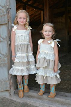 country flower girls in linen and lace ruffled handmade dresses with ribbon ties at shoulders.  Cute tan and turquoise boots perfect the look!