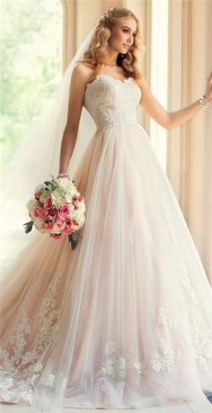 A blend of an A-line and a ball gown with a skirt of blush colour to off show and bring attention to the delicate lace work.