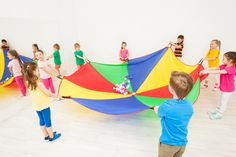 Happy children playing parachute games in gym Stock Photo , Parachute Games, Montessori Math, Reggio Emilia, Happy Kids, Childcare, Kids Playing, Cool Kids, Beach Mat, Outdoor Blanket