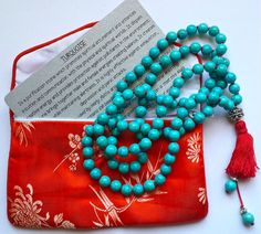Turquoise Mala with red cord and tassel.