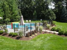 Exterior: Black Iron Fences Around Pool Landscaping Ideas In Some Brick Wall Design Of House With Small Round Pool And Furniture Chairs In Large Yard from 27 Great Pool Landscaping Ideas Designs Fence Around Pool, Landscaping Around Pool, Swimming Pool Landscaping, Small Backyard Pools, Fence Landscaping, Large Backyard, Backyard Fences, Landscaping With Rocks, Luxury Landscaping