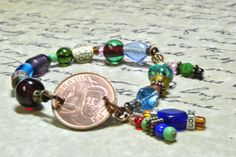5 Centavos Brazilian coin bracelet with multi color glass beads.  Bronze and silver beads mixed through out.  Stretch cord and wire wrapping.