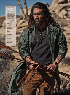 Starring in a GQ photo shoot, Jason Momoa wears a Prada coat with a POLO Ralph Lauren henley, Duluth Trading Company pants, and an Eleventy Belt.