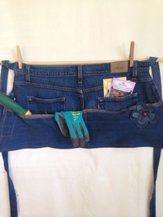 This upcycled denim garden/ utility /vendor half apron features 5 functional pockets. It has 2 jean pockets great for holding seed packets, gloves