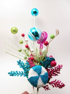 The height of the tallest Christmas bulb is a little over 8 inches high, so this fascinator is highly visible and made to show off your holiday spirit! I think it is best viewed when worn on the left side with the pink lollypop toward the back. You will be the envy of everyone this season!