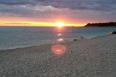 Zalazak sunca,zaljubljeni parovi,uzivaju,odmor,more,plaze,pijesak,kamenje
