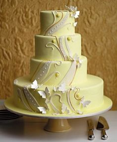 Pale yellow fondant and features an intricate design inspired by wild vines that are created with lines, swirls and dots. Sugar paste butterflies adorn the edges, as though in mid-flight.