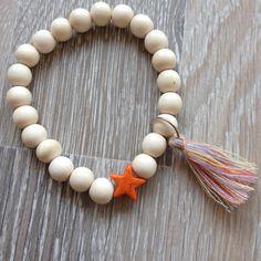 Armband van 9mm amandel hout met meerkleurig kwastje en een oranje howliet ster. Van JuudsBoetiek, €3,50. Te bestellen op www.juudsboetiek.nl.
