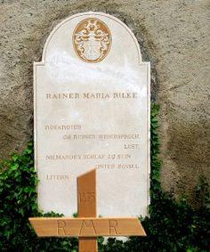 """Rainer-Maria-Rilke-Grab[. Sulla lapide del suo sepolcro accanto alla chiesetta sulla collina di Raron, Rilke farà incidere lo stemma di famiglia e la frase: """"Rosa, contraddizione pura, desiderio di essere il sonno di nessuno sotto tante palpebre."""""""