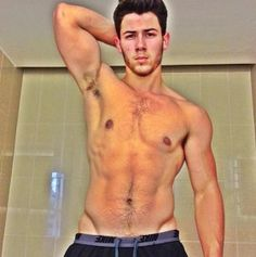 Who could ever guess that Nick Jonas was hiding a buff body under his shirt?