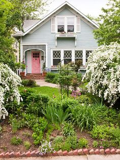 I love the window boxes, trellis around the pink front door, and variety of plants here. That edging is crap though!