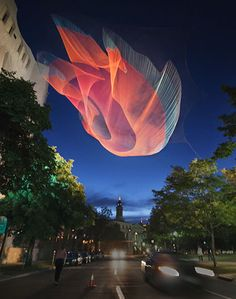 Janet Echelman makes huge, sculptural nets that are colorful and billowing during the day, and light up the skyline like beautifully bizarre jellyfish at night.