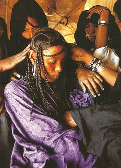 """"""" In the privacy of her mother's tent, a fifteen-year-old bride is prepared for her wedding. Her hair is plaited by the wife of the blacksmith, who is believed by the Tuareg to possess special powers of sorcery. The Tuareg insist that a bride's hair. We Are The World, People Of The World, African Tribes, African Women, African Hairstyles, Afro Hairstyles, Natural Hair Growth, Natural Hair Styles, Skin Girl"""
