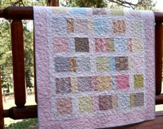 This bright and happy Handmade quilt is made with fabrics from the le elephant collection. Pretty shades of pink, blue, gray, green and yellow are printed with elephants, flowers, alphabets, dots, checks, squiggly stripes. These are all pieced together in a random, scrappy design. The white border makes all the colors stand out so well.  The quilt measures 41 x 48.....this is a perfect size for a crib, to use on the floor for playtime, on your lap for snuggling or tossed across a chair. It…