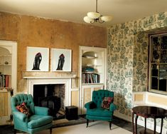 At Hauser & Wirth's farmhouse/gallery space, photographs by Roni Horn hang above the mantel in the living room. The tufted armchairs were co...