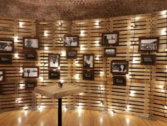 A custom wall and poseur table made from reclaimed pallets, festoon lighting adorns the pallet wall to highlight the rustic bespoke picture frames.
