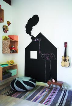 Вам потребуется: грифельная краска, кисть, валик и ванночка для валика, малярная лента, карандаш, линейка белый мел для доски. 1Домик нарисуйте от руки прямо на стене или же на упаковочной бумаге в натуральную величину, а затем переведите контуры на стену. Шаблон из бумаги имеет свои преимущества, так как форму и размер мотива можно корректировать. 2На неприметном
